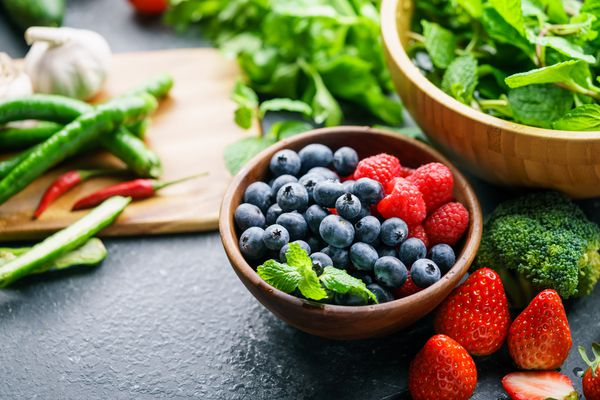 Bowl of berries on table with other various vegetables