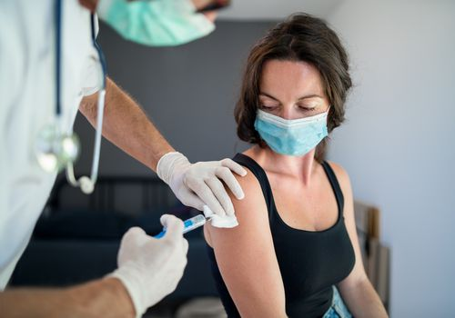 Woman receiving a vaccine while wearing a face mask.