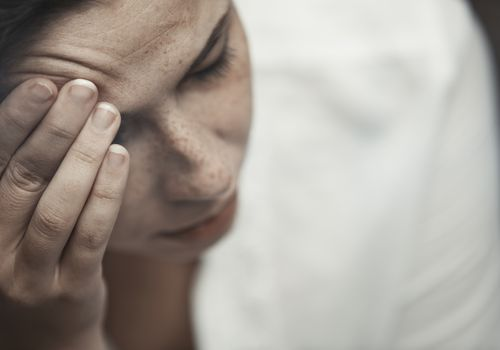 Depressed woman with her hand on her head