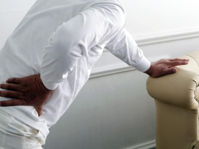 a man holding his hip in pain