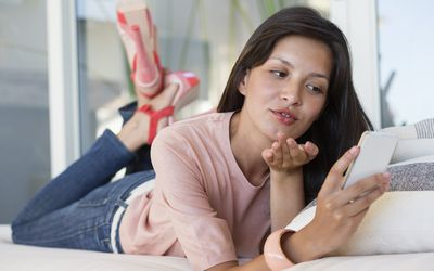 Woman reading text message on a mobile phone and giving flying kiss