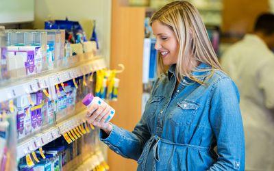 Pregnant mother reading prenatal vitamin label in pharmacy