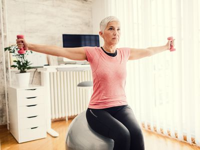Woman sitting on an exercise ball doing chest flys with dumbbells