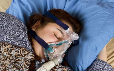 A brunette woman sleeping with a cpap mask on