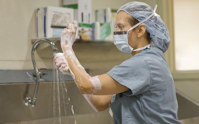 Surgical nurse scrubs her hands