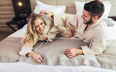 Couple in bathrobes laughing on a bed in a hotel