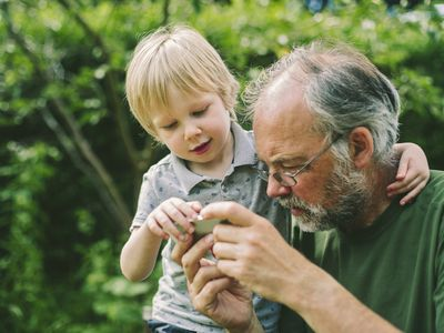 Child and grandfather watching video together
