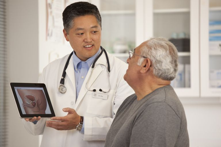 Doctor using digital tablet to talk to senior man.