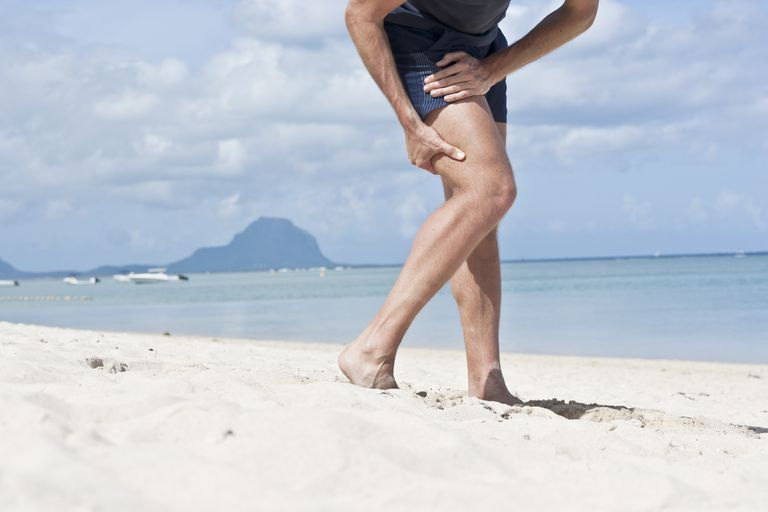 Man on the beach holding his hamstring