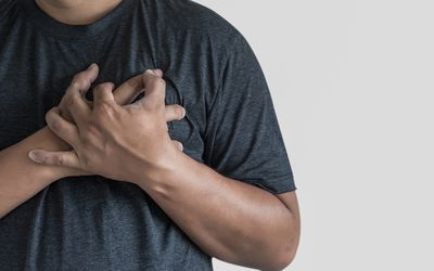 A Black man holding his chest
