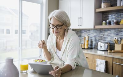 Woman eating fruit salad and using digital tablet