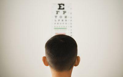 Young boy looking at wall eye chart