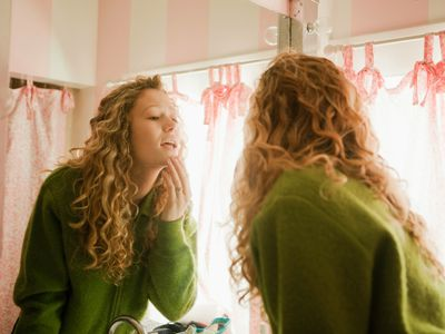 Teenage girl checking skin in bathroom mirror