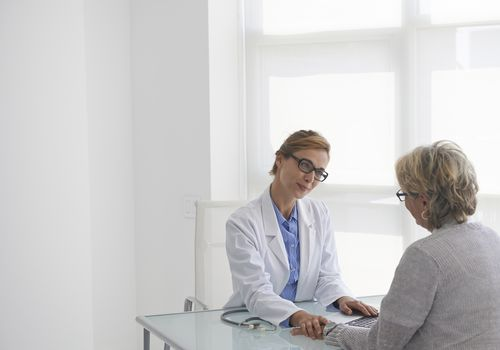 Caucasian doctor and patient talking in office