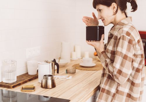 woman in flannel smelling a candle