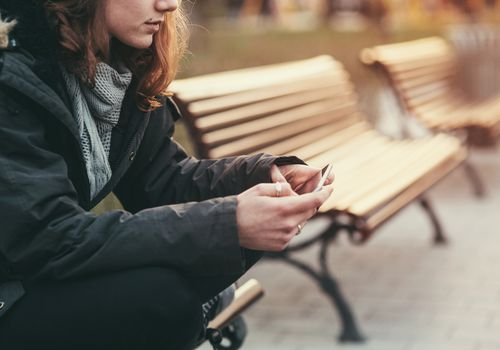Woman looking at cell phone on park bench.