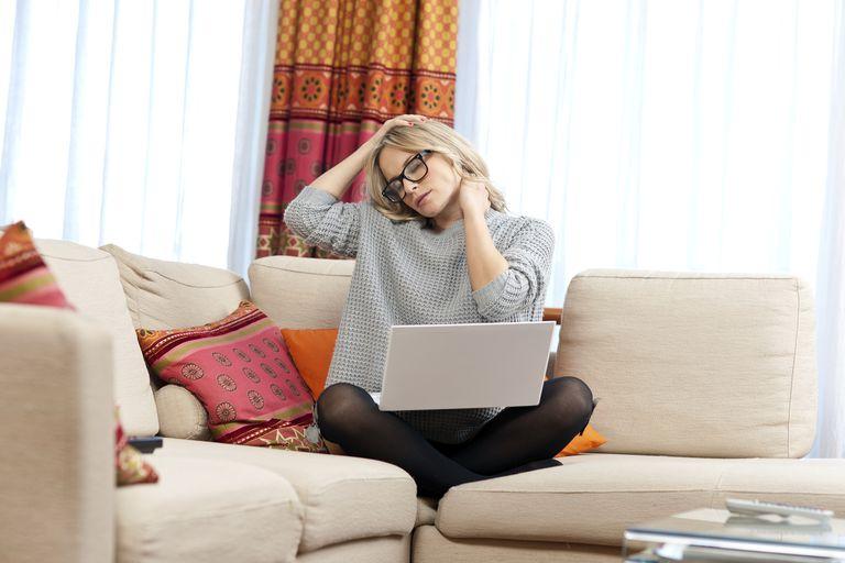 Woman working on laptop, massaging neck