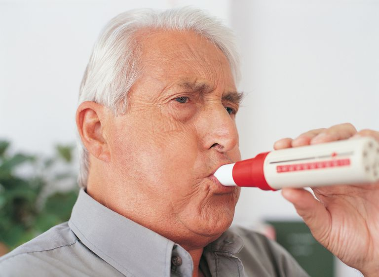 Elderly male patient using spirometer device