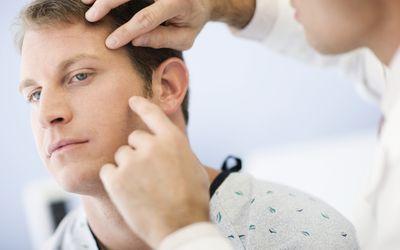 Doctor examining man's skin