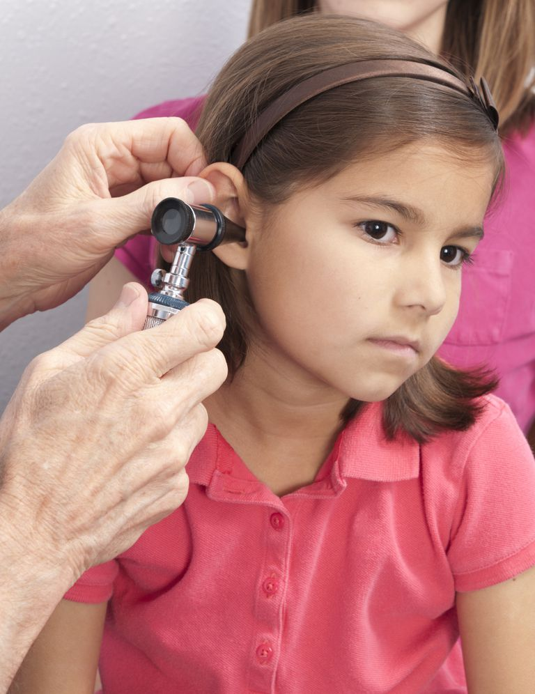 A young girl being examined by her pediatrician.