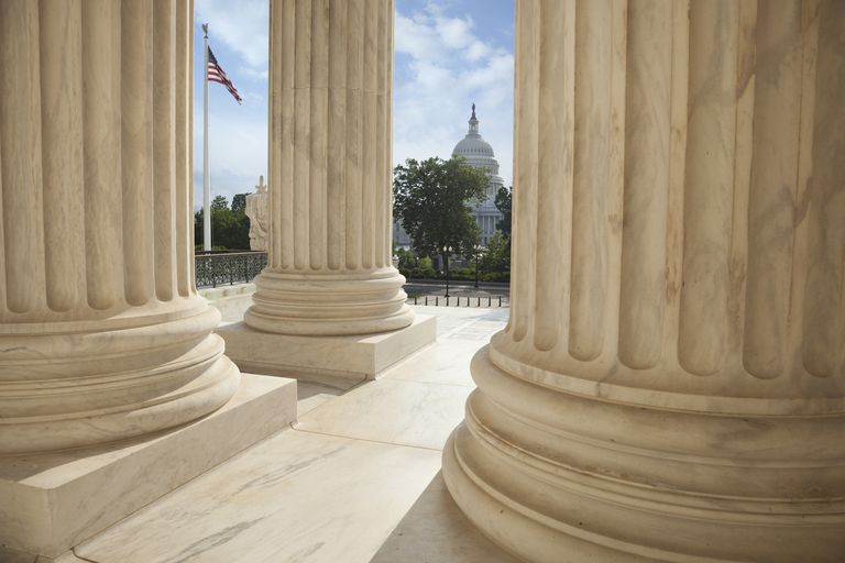 Supreme Court columns with American flag and US Capitol