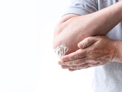 a man rubbing cream on his elbow