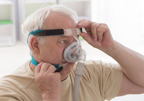 Senior man wearing a sleap apnea treatment mask