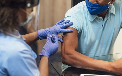 Man receiving a vaccine shot in the arm.