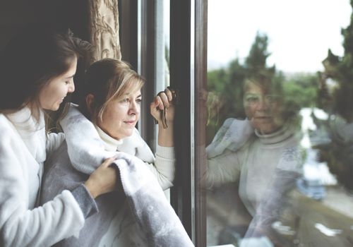 Young woman wrapping a blanket around an older woman at window