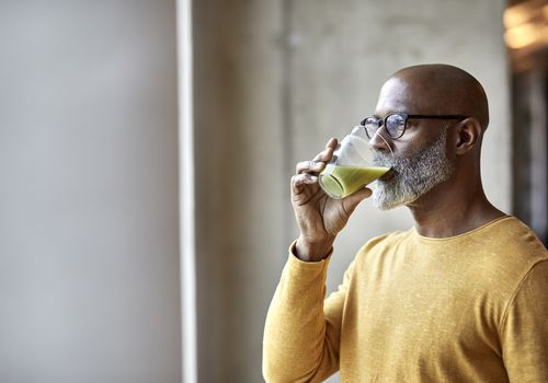 Mature businessman in office drinking a smoothie - stock photo