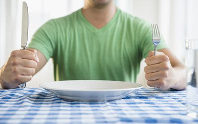 Mixed race man with fork and knife