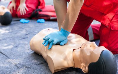 Midsection Of Man With Cpr Dummy During Training