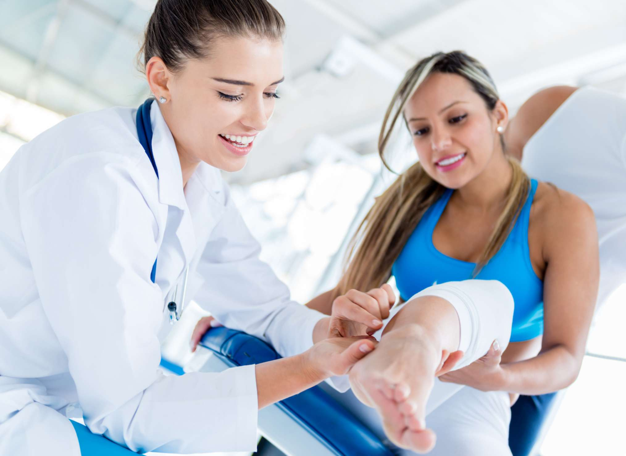 Doctor adjusts a woman's ankle in physical therapy