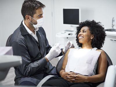 Women in dental chair speaking with dentist