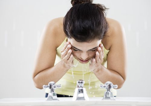 Woman washing face in the sink