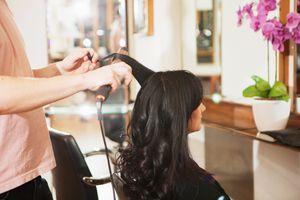 Hair dresser styling woman's hair