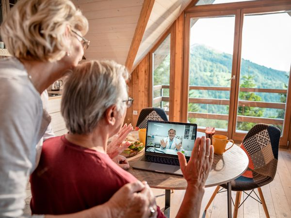 Older couple views a health professional over a laptop on their kitchen table.