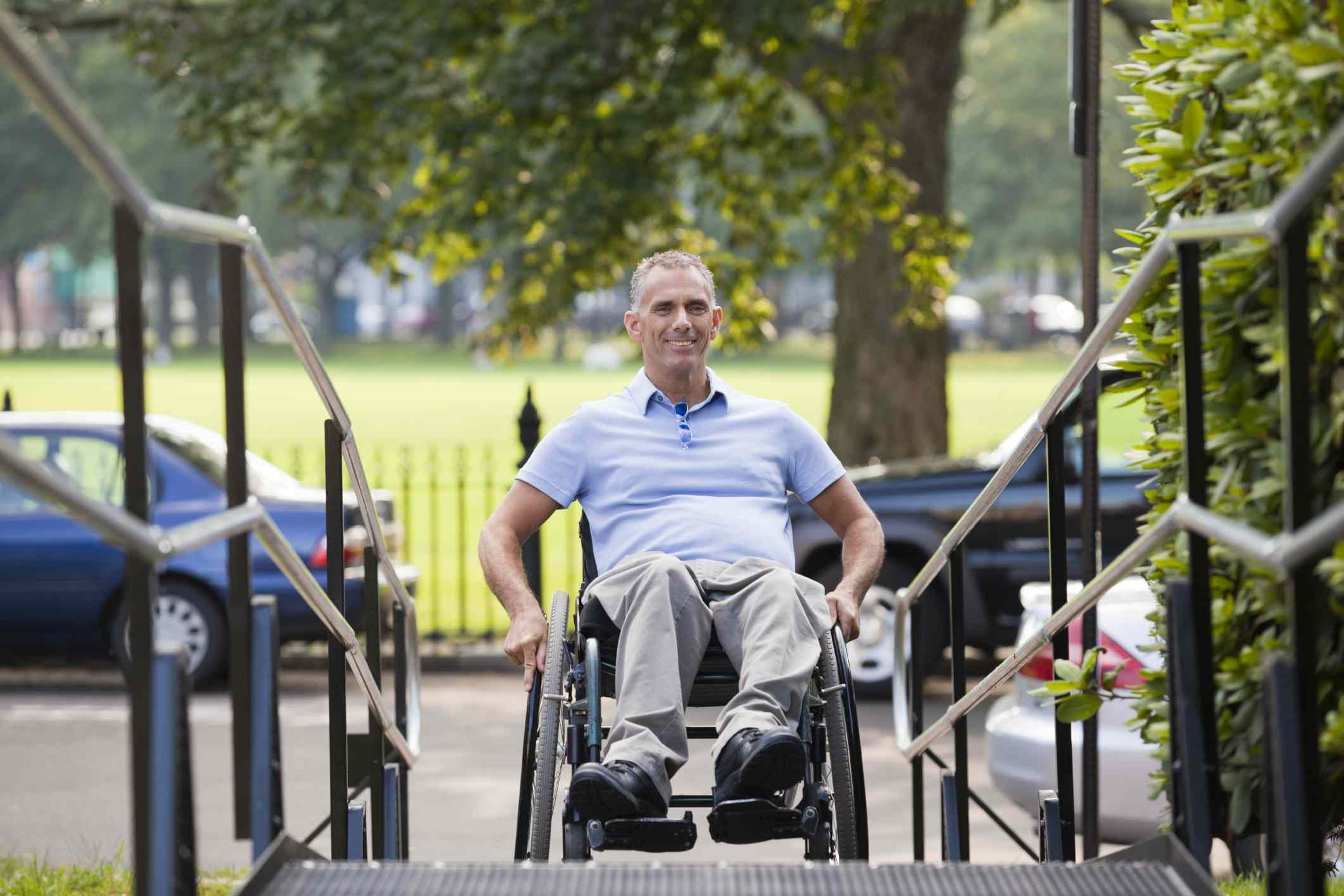 Man with spinal cord injury in wheelchair moving up an outdoor wheelchair ramp