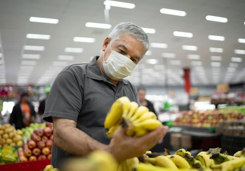 Man grocery shopping wearing a mask and holding bananas.