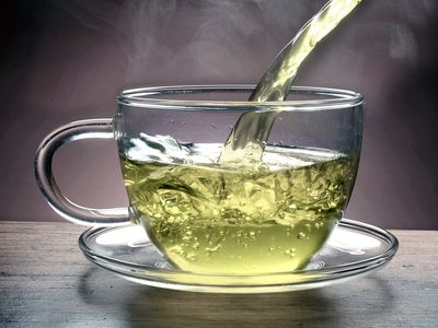 The pouring of hot herbal tea into a clear mug
