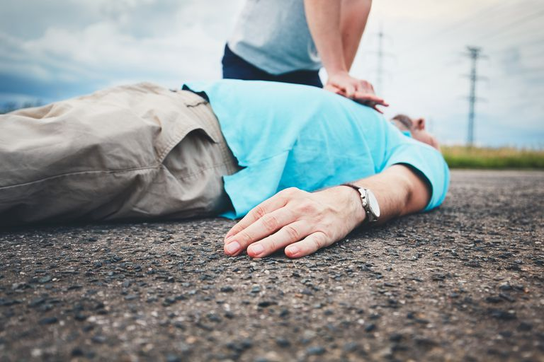 Midsection Of Man Resuscitating Friend Lying On Road