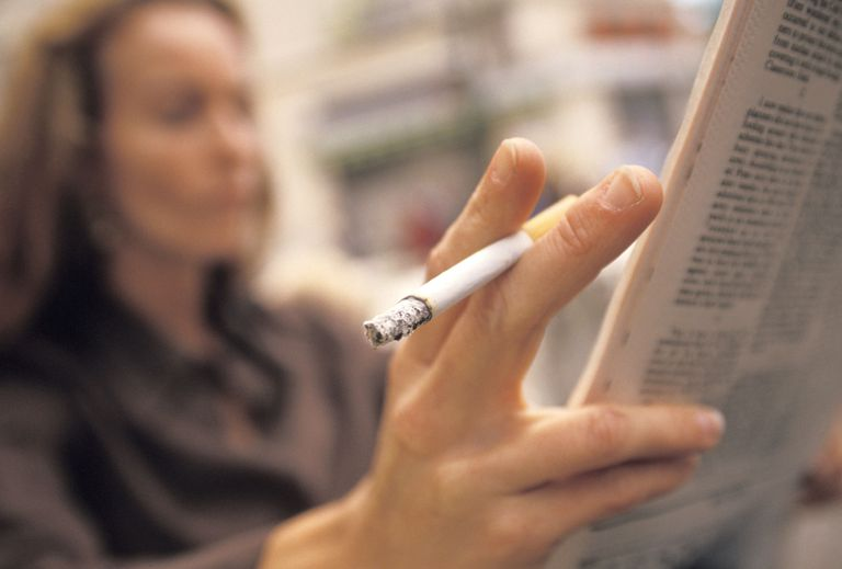Woman smoking while reading a paper