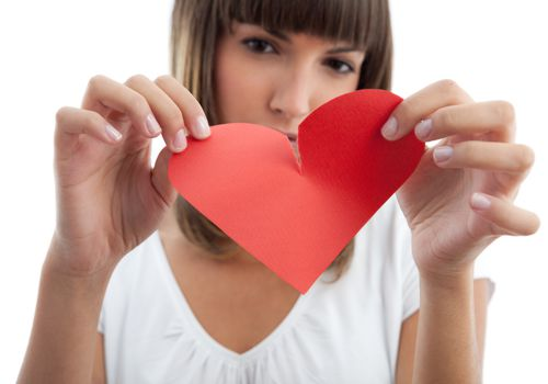 Woman tearing a paper heart in half