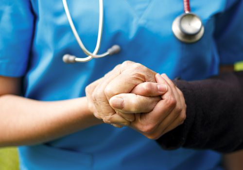 Nurse holding a senior person's hand