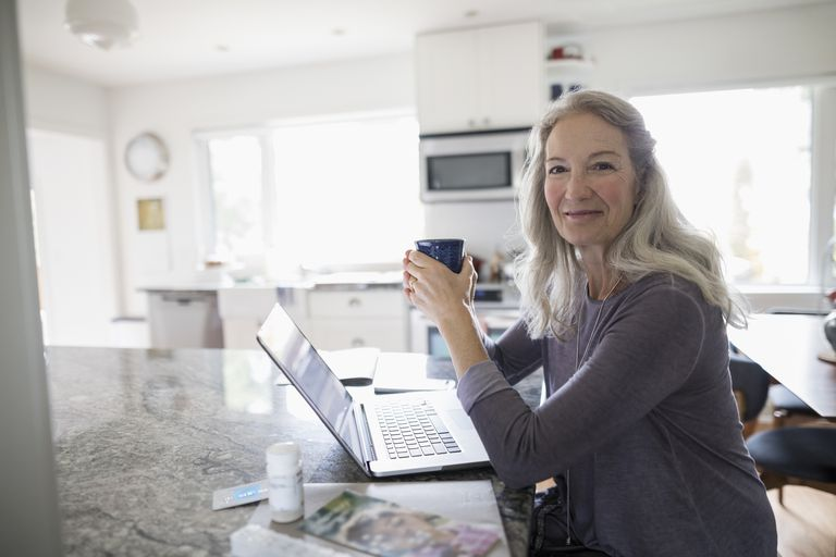middle aged woman working on computer smiling at camera