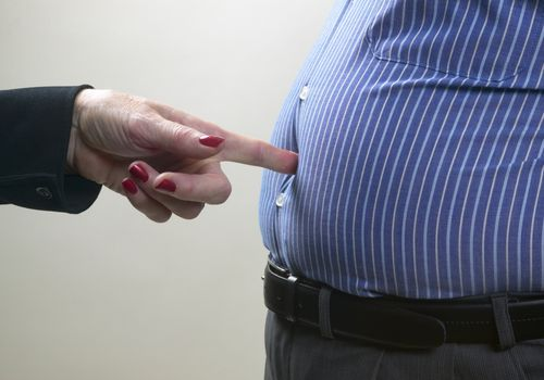 a woman poking a man's belly