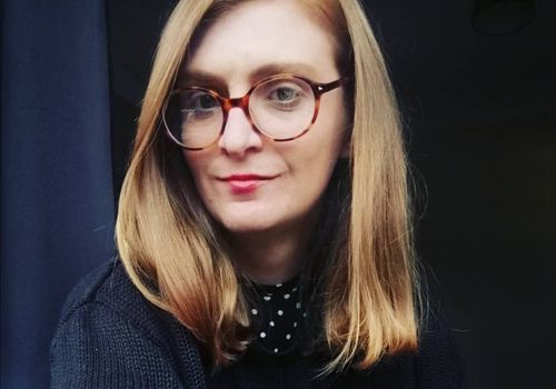 a white woman with auburn hair wearing round glasses and a black jumper