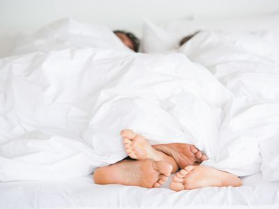 Two people under the covers in bed