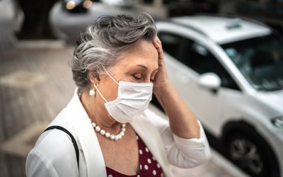 Senior businesswoman with mask feeling bad at street