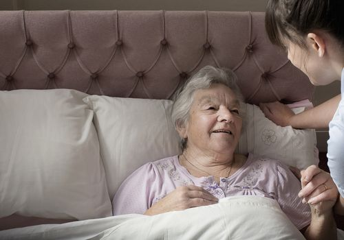 A personal care assistant chatting with a senior woman who is in bed